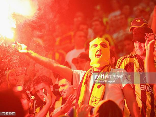 Fenerbahce fan holds a smoke bomb during the Sueper Kupa Cup match between Fenerbahce SK and Besiktas JK at the Rhein Energie stadium on August 5,...