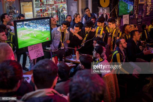 Fenerbahce fans react as they watch the Istanbul Derby match between Fenerbahce and Galatasaray in a bar on March 17 2018 in Istanbul Turkey The...