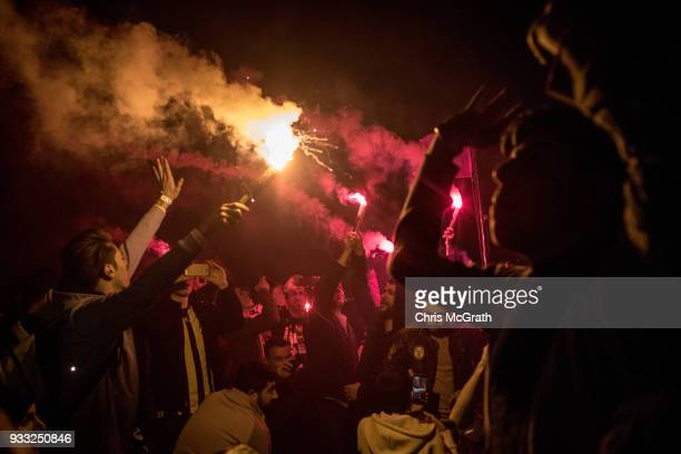 Fenerbahce fans sing songs and wave flares as they ride the ferry back to Istanbul's European side after watching the Istanbul Derby match between...