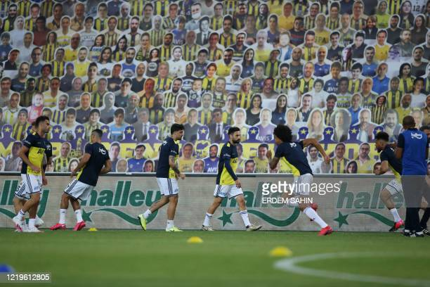 Fenerbahce players warm up in front of cardboards with photographs of Fenerbahce fans on the stands ahead of the Turkish Super League football match...