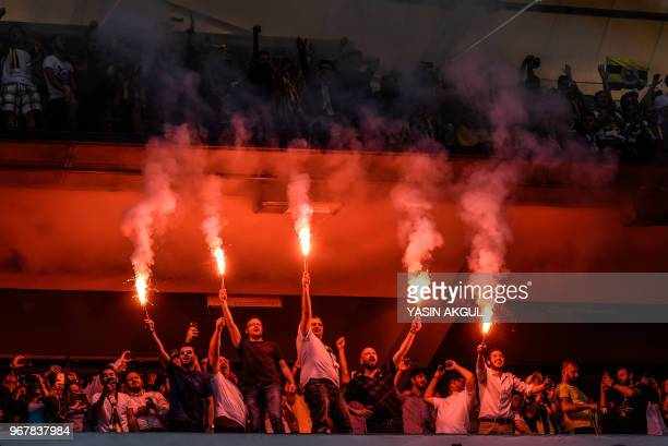 Fenerbahce supporters hold burning flares during a gathering with the newly elected Fenerbahce chairman at the Ulker Stadium in Istanbul on June 5 in...