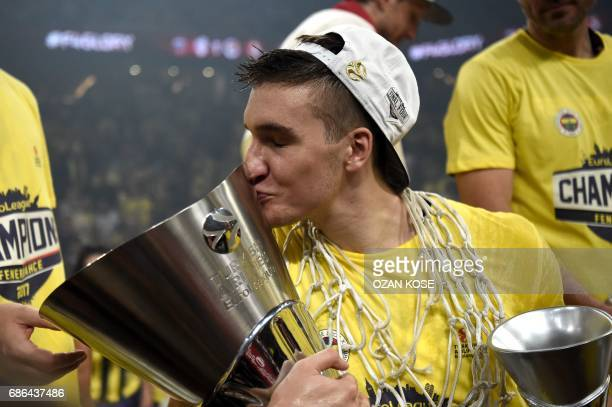 Fenerbahce's Bogdan Bogdanovic kisses the trophy as he celebrates winning the first place basketball match between Fenerbahce and Olympiacos at the...