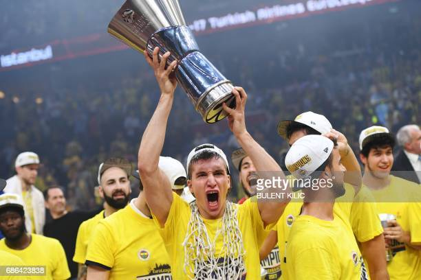 Fenerbahce's Bogdan Bogdanovic reacts with the trophy as he celebrates winning the first place basketball match between Fenerbahce and Olympiacos at...