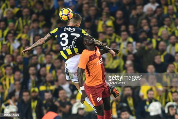 Fenerbahce's defender Martin Skrtel heads the ball next to Galatasaray's Bafetimbi Gomis during Turkish Spor Toto Super league fotball match between...