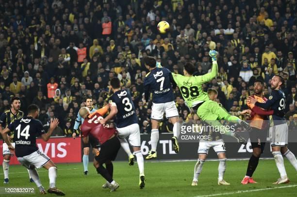 Fenerbahce's goal keeper Altay Bayindir blocks the ball next to Galatasaray's Sofiane Fehouli and Henry Onyekuru during the Turkish Super league...