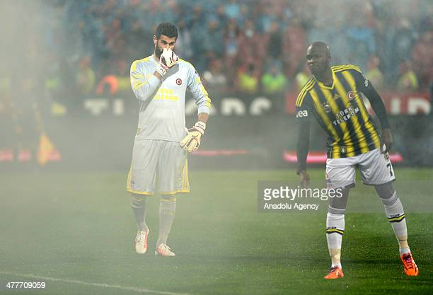 Fenerbahce's goalkeeper Volkan Demirel and Moussa Sow react to dangerous objects thrown onto pitch during the Turkish Spor Toto Super League's...