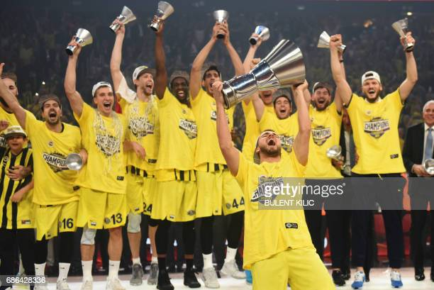 Fenerbahce's Melih Mahmutoglu reacts with the trophy as he and teammates celebrate winning the first place basketball match between Fenerbahce and...