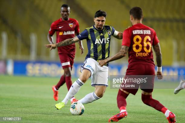 Fenerbahce's Ozan Tufan vies for the ball with Kayserispor's Diego Angelo de Oliveira during the Turkish Super League football match between...