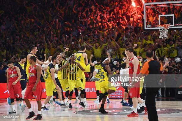Fenerbahce's players celebrate winning as Olympiacos' react after the first place basketball match between Fenerbahce and Olympiacos at the...