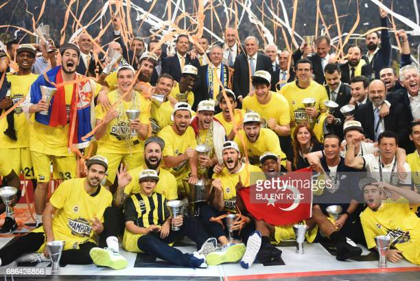 Fenerbahce's players pose with the trophy as they celebrate winning the first place basketball match between Fenerbahce and Olympiacos at the...