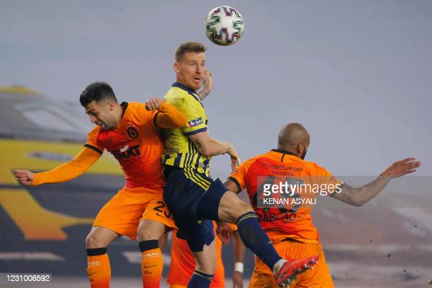 Fenerbahce's Turkish defender Serdar Aziz heads the ball next to Galatasaray's Turkish defender Emre Tasdemir and Brazilian defender Marcau during...