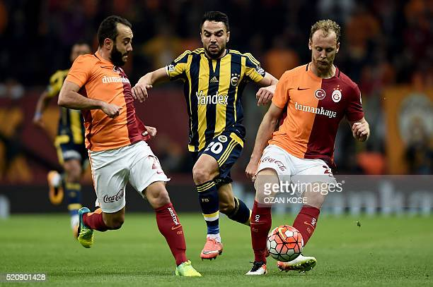 Fenerbahce's Volkan Sen vies with Galatasaray's Semih Kaya and Emre Colak during the Turkish Spor Toto Super league football match between...