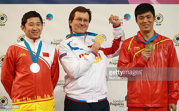 Feng Ding of China Alexei Klimov of Russia and Jian Zhang of China stand on the podium for the Men's 25m Rapid Fire Pistol competition on day nine of...