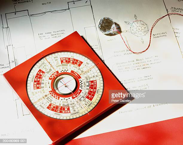 feng shui compass and crystal on house plan, close-up, elevated view - feng shui stock photos and pictures