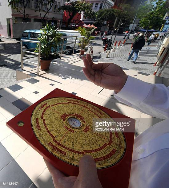 Feng Shui master Jet Li shows the reading from a compass for a building entrance in Singapore on January 21, 2009. Fengshui experts say the earth...