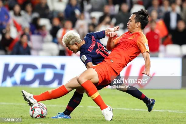 Feng Xiaoting of China competes with Chanathip Songkrasin of Thailand during the AFC Asian Cup round of 16 match between Thailand and China at Hazza...