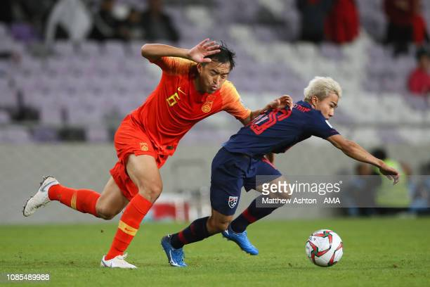 Feng Xiaoting of China tangles with Chanathip Songkrasin of Thailand during the AFC Asian Cup round of 16 match between Thailand and China at Hazza...