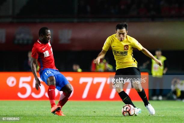 Feng Xiaoting of Guangzhou Evergrande and Christian Bassogog of Henan Jianye compete for the ball during the seventh round match between Guangzhou...