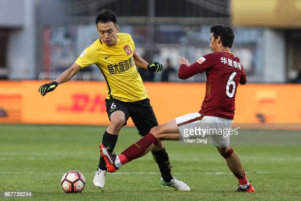Feng Xiaoting of Guangzhou Evergrande dribbles past Luo Senwen of Hebei China Fortune during the Chinese Super League match between Hebei China...