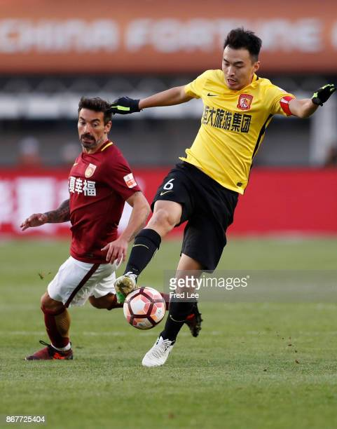 Feng Xiaoting of Guangzhou Evergrande holds off the challenge from Ezequiel Lavezzi of Hebei China Fortune during the Chinese Super League match...