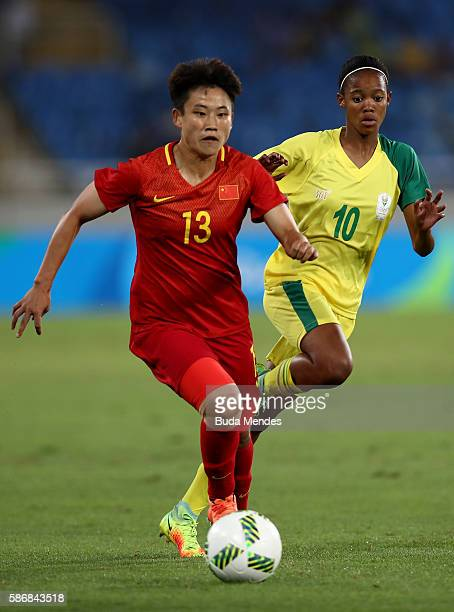 Fengyue Pang of China runs with the ball against Linda Motlhalo of South Africa during the Women's Group E first round match between South Africa and...