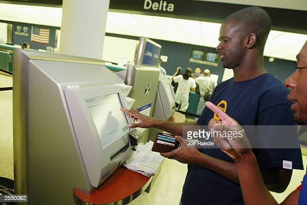 Fenton Bratford and Steve Roberts use a computer to purchase their e-tickets at the Delta airlines counter in the Miami International Airport...