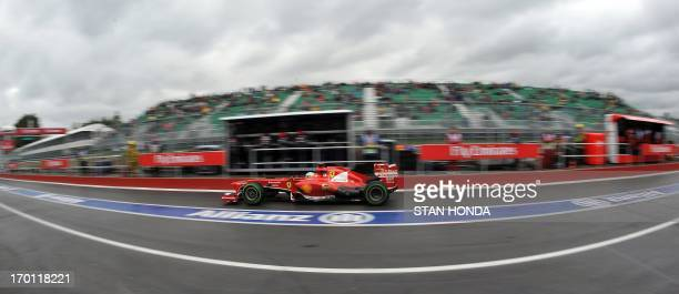 Ferarri driver Fernando Alonso of Spain drives through the pits during practice at the Canadian Formula One Grand Prix at the Circuit Gilles...