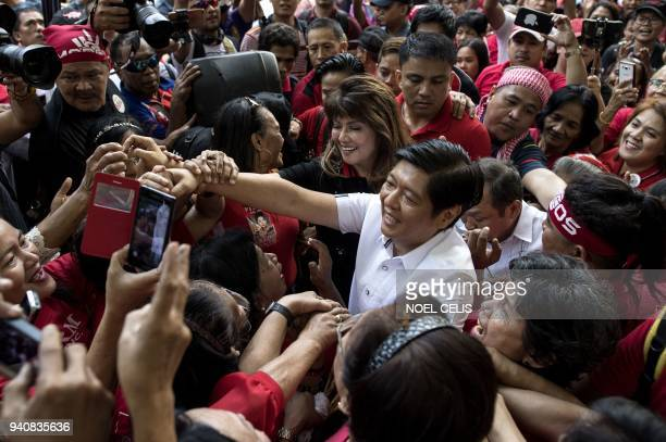TOPSHOT Ferdinand Bongbong Marcos Jr former senator and son of the late dictator Ferdinand Marcos is surrounded by supporters after attending the...