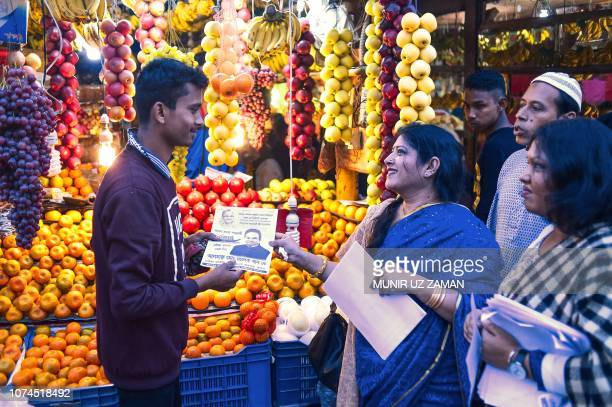 TOPSHOT Ferdousi Khan the wife of Bangladesh Awami League election candidate Sadek Khan distributes leaflets to voters during the general election...