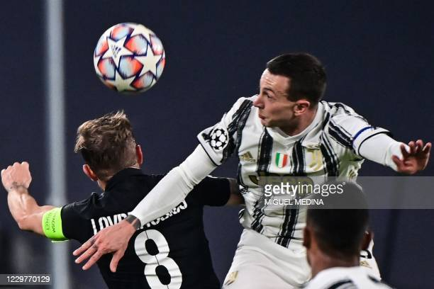 Ferencvaros' Hungarian forward Gergo Lovrencsics and Juventus' Italian forward Federico Bernardeschi go for a header during the UEFA Champions League...