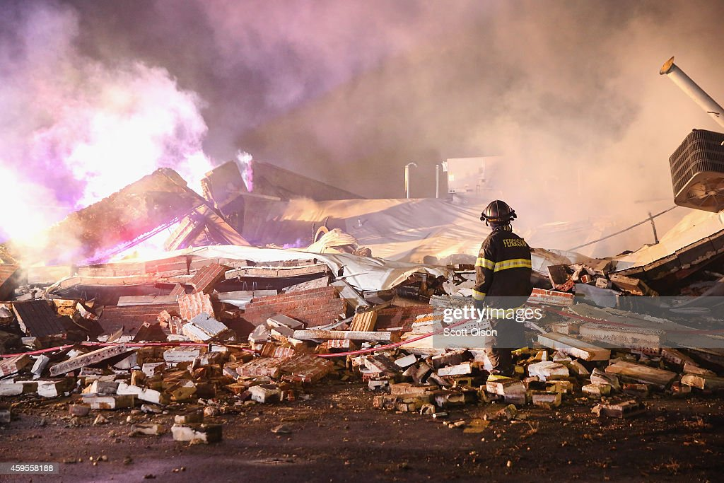 A Ferguson firefighter surveys damage to a strip mall that was set on fire when rioting erupted following the grand jury announcement in the Michael Brown case on November 25, 2014 in Ferguson, Missouri. Brown, an 18-year-old black man, was killed by Darren Wilson, a white Ferguson police officer, on August 9. At least 12 buildings were torched and more than 50 people were arrested during the night-long rioting.