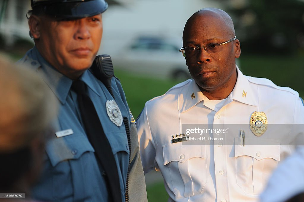 Ferguson Police Officer Greg Casem and Police Chief Andre Anderson comfort mourners during a candlelight vigil held in honor of Jamyla Bolden on August 20, 2015 in Ferguson, Missouri. Casem carried Jamyla Bolden, 9, to an ambulance after she was allegedly struck by a stray bullet from a drive-by shooting and killed while doing her homework at her home in Ferguson on August 18th.