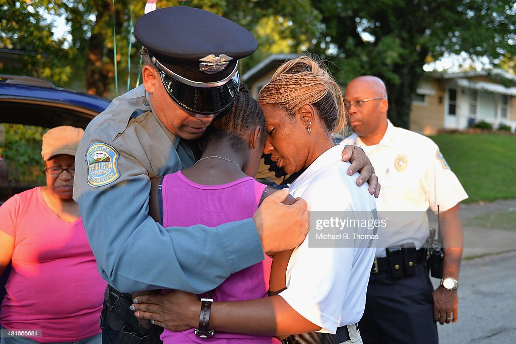 Ferguson Police officer Greg Casem and Sergeant Dominica Fuller console a mourning child during a candlelight vigil held in honor of Jamyla Bolden on August 20, 2015 in Ferguson, Missouri. Casem carried Jamyla Bolden, 9, to an ambulance after she was allegedly struck by a stray bullet from a drive-by shooting and killed while doing her homework at her home in Ferguson on August 18th.