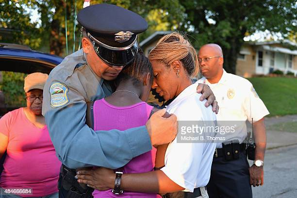 Ferguson Police officer Greg Casem and Sergeant Dominica Fuller console a mourning child during a candlelight vigil held in honor of Jamyla Bolden on...