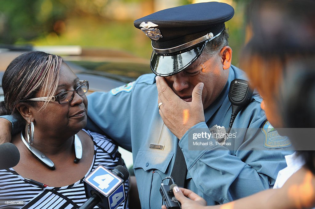 Ferguson Police officer Greg Casem is overcome with emotion during a candlelight vigil held in honor of Jamyla Bolden on August 20, 2015 in Ferguson, Missouri. Casem carried Jamyla Bolden, 9, to an ambulance after she was allegedly struck by a stray bullet from a drive-by shooting and killed while doing her homework at her home in Ferguson on August 18th.