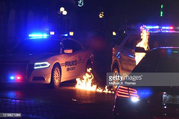 Ferguson police officer reacts as a flammable object is thrown a a police cruiser following a protest at the Ferguson Police Department on May 31,...