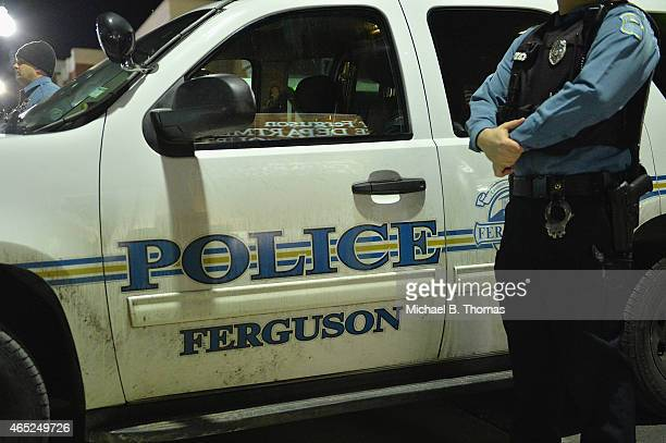 Ferguson police officer stands on watch as protestors demonstrate outside the Ferguson Police Department in Ferguson Missouri on March 4 2015 The...