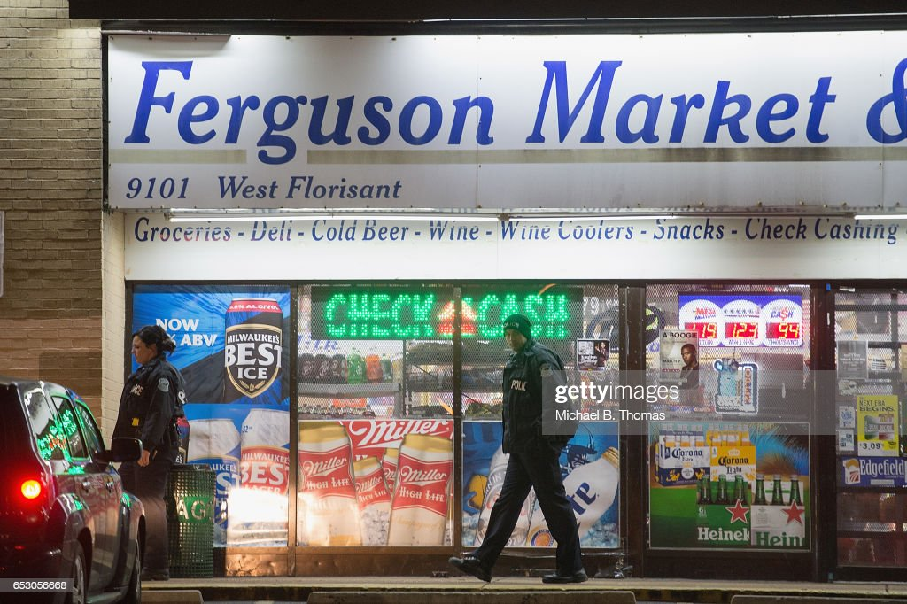 Ferguson police officers are seen outside a storefront as demonstrators protests outside the Ferguson Market and Liquor on March 13, 2017 in Ferguson, Missouri. Tension and protest in Ferguson has arisen in response to video footage of slain 18 year-old Michael Brown in a recent documentary.