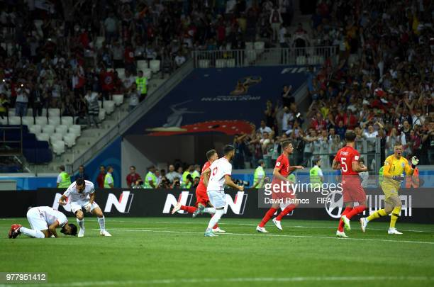 Ferjani Sassi of Tunisia celebrates after scoring his team's first goal from a penalty with team mate Ali Maaloul as England players look dejected...
