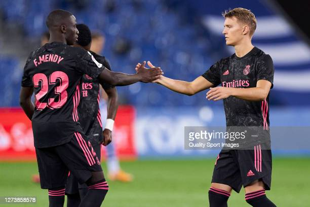 Ferland Mendy and Martin Odegaard of Real Madrid salutes during the La Liga Santader match between Real Sociedad and Real Madrid at Estadio Anoeta on...