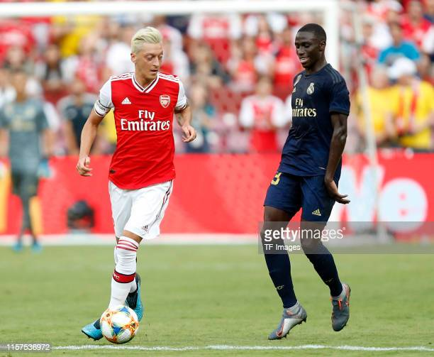 Ferland Mendy of Real Madrid and Mesut Oezil of Arsenal battle for the ball during the 2019 International Champions Cup match between Real Madrid and...