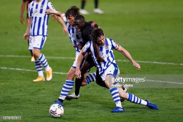 Ferland Mendy of Real Madrid is challenged by Robin Le Normand and Aritz Elustondo of Real Sociedad during the La Liga Santander match between Real...
