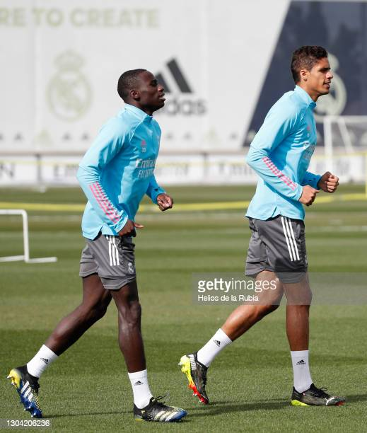 Ferland Mendy with Raphaël Varane of Real Madrid CF warm up during a training session at Valdebebas training ground on February 26, 2021 in Madrid,...