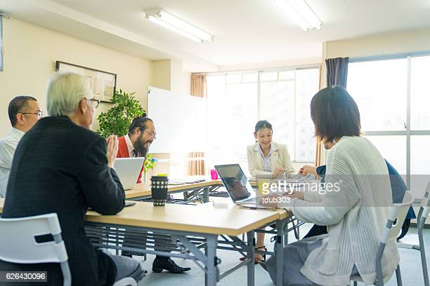 fermale teacher with adult students in community college - community centre stock pictures, royalty-free photos & images