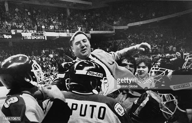 Fern Flaman Northeastern University's hockey coach being hoisted to team players' shoulders after a win over Boston College in the Beanpot final...