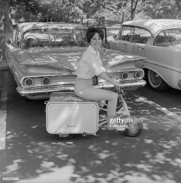 Fern Lynn demonstrating the Valmobile Suitcase Scooter New York State 1962 The Valmobile folds into a package the size of a suitcase and fits into a...