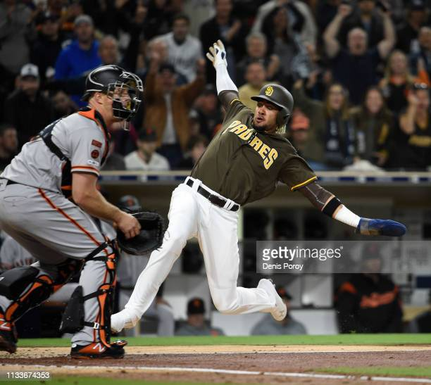 Fernadndo Tatis Jr #23 scores ahead of the throw to Erik Kratz of the San Francisco Giants during the second inning of a baseball game at Petco Park...