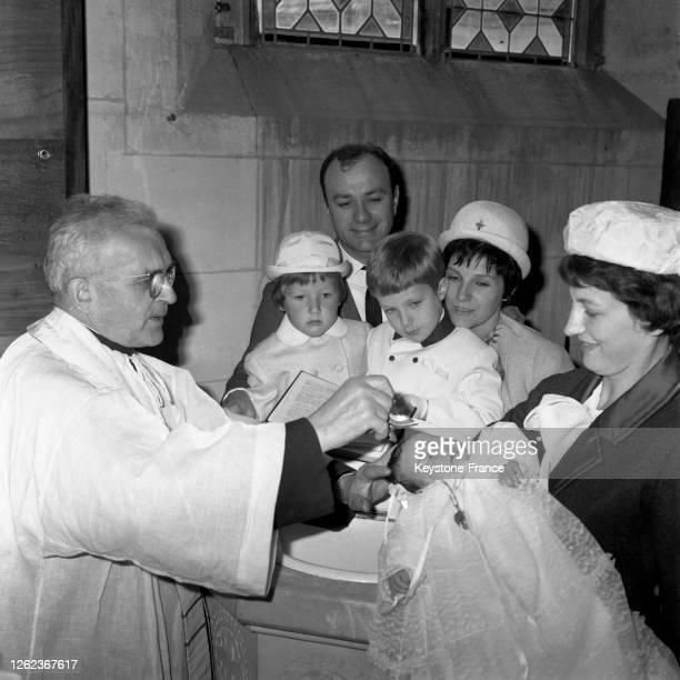 Fernand Raynaud, un peu ému, regarde sa fille Françoise se faire baptiser dans les bras de sa marraine Francine Le Gent, à ses côtés Madame Fernand...