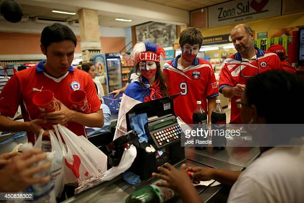 Fernanda Gomez and her brother Agustin Gomez show their support for the Chilean soccer team as they check out at a grocery store after attending the...