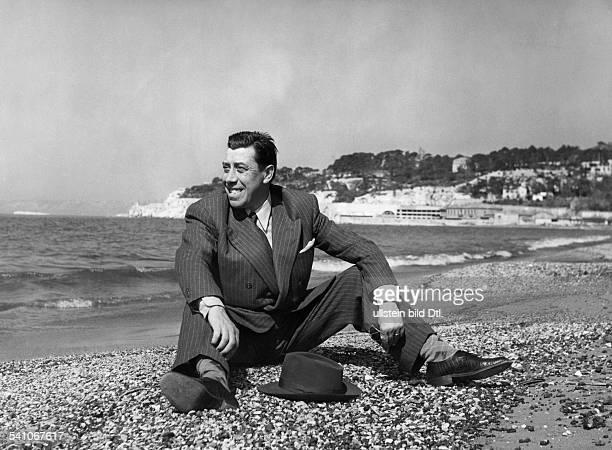 Fernandel *Schauspieler Frankreich Ganzkoerperaufnahme am Strand von Marseille 1955